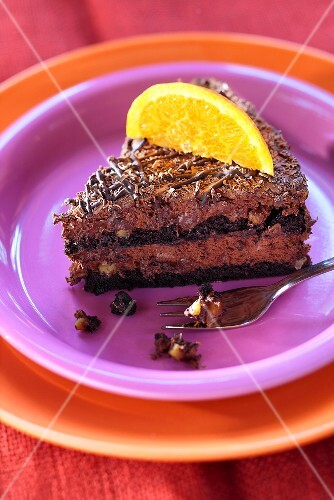 Piece of chocolate mousse cake with a slice of orange