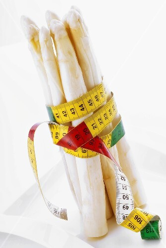White asparagus wrapped in tape measure