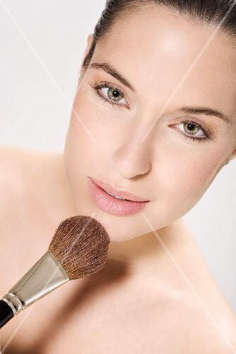 Young woman using make up brush, portrait