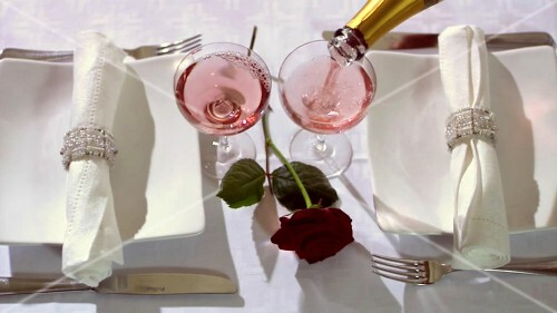 Elegantly laid table with red rose and rosé wine