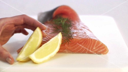 Garnishing gravlax with lemon (close-up)