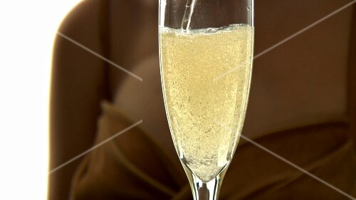 Pouring and drinking a glass of sparkling wine