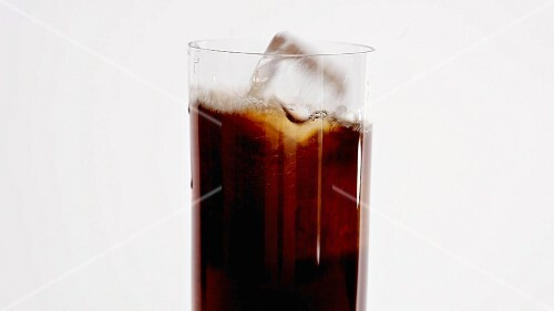 Pouring cola into a glass and adding ice cubes