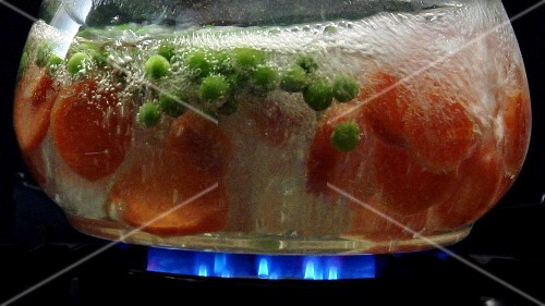 Cooking peas and carrot slices in hot water