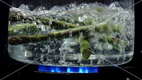 Asparagus tips falling into boiling water