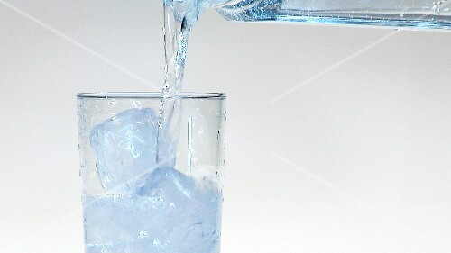 Pouring mineral water into a glass of ice cubes