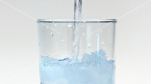 Pouring water into a glass of crushed ice (close-up)