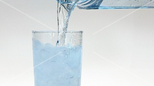 Pouring water into a glass of crushed ice