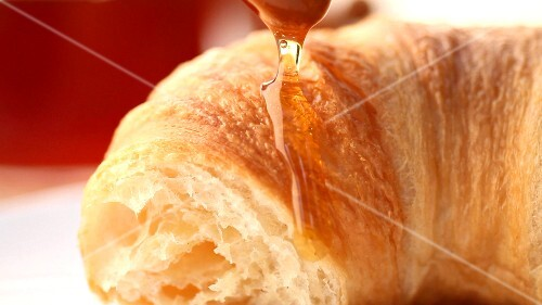 Croissant with honey (close-up)
