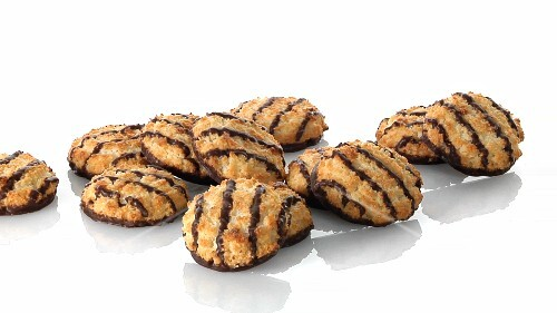 A pile of coconut macaroons with chocolate glaze and a hand taking one