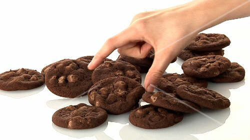 A pile of chocolate chip cookies and a hand taking one