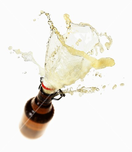 Beer splashing out of brown bottle