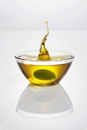 Green olive falling into glass dish of olive oil