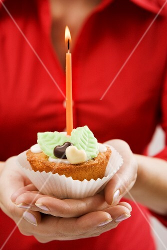 Woman holding cupcake with marzipan leaves and candle