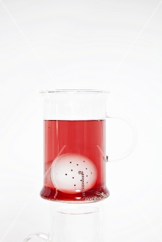 Fruit tea in glass with tea infuser