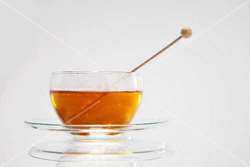 Tea with sugar swizzle stick in glass cup and saucer