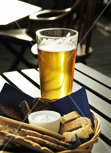 Glass of lager and bread basket on table in restaurant