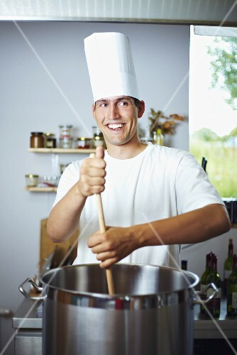 Laughing chef stirring pan