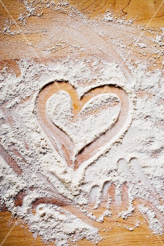 Heart drawn in flour on wooden background