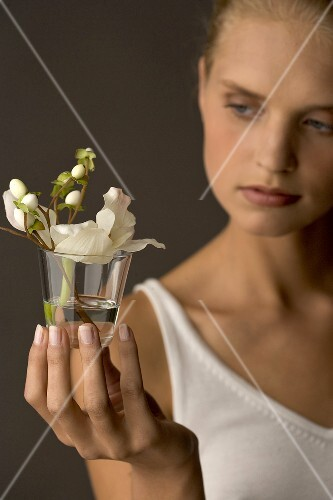Young woman holding glass with white Christmas rose