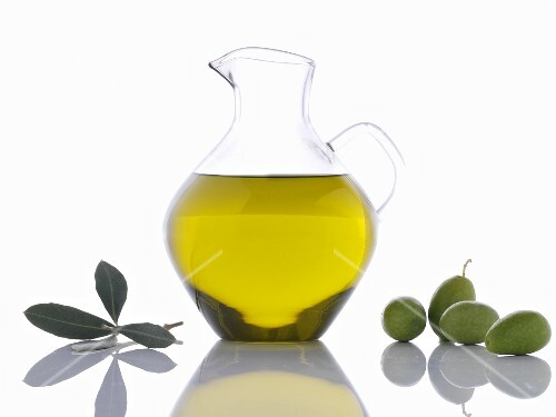 Olive oil in carafe, green olives and olive leaves