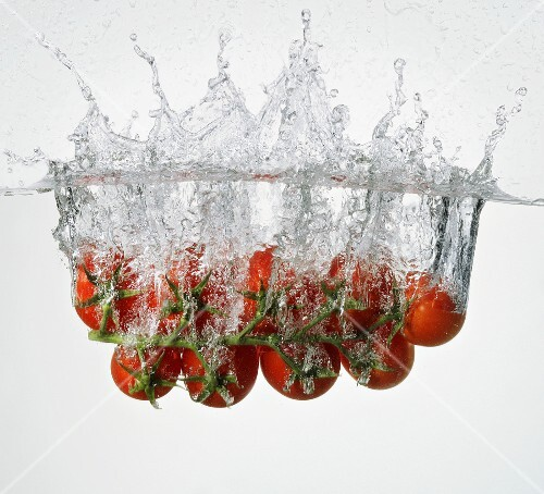 Vine tomatoes falling into water
