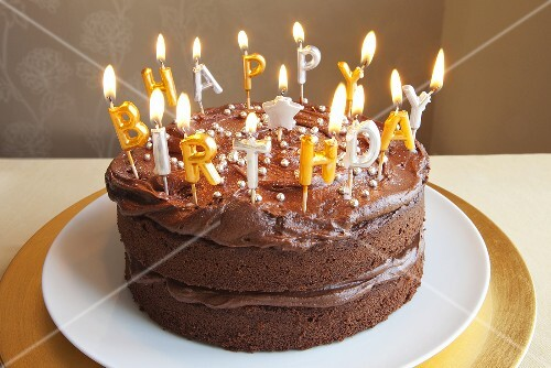 A chocolate birthday cake with lots of candles