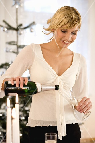 Young woman pouring champagne