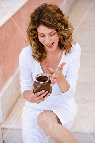 Woman sneaking a fingerfull from a jar of chocolate spread