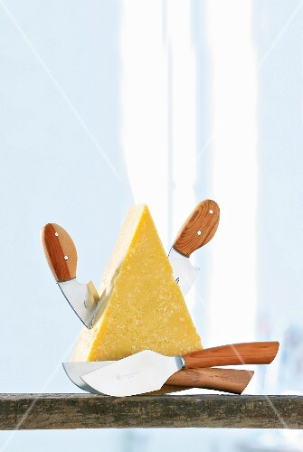 A piece of cheese with cheese knives
