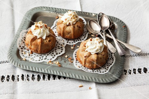 Mini damson and hazelnut Bundt cakes topped with cream on tray with spoons