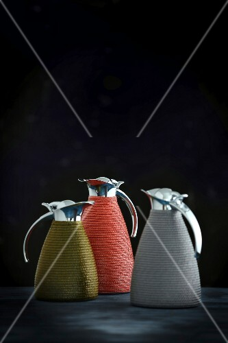Three different coloured Thermos jugs