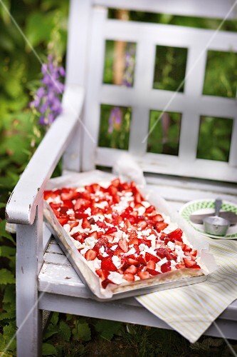 Strawberry tray bake cake outside on a garden bench