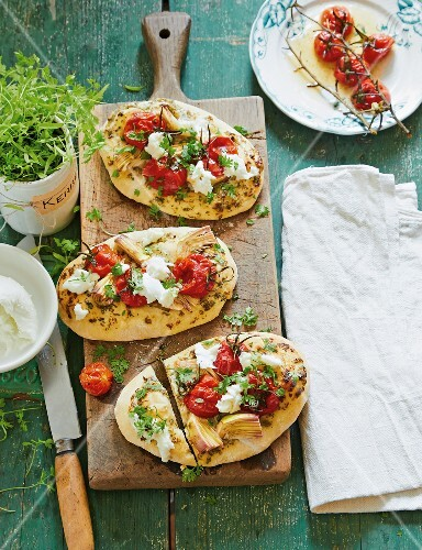 Pizza pitas with tomatoes, artichokes, mozzarella and chervil