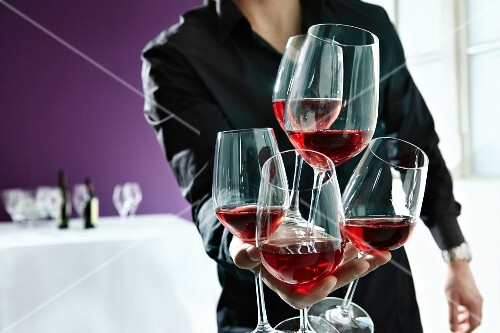 A waiter holding lots of glasses of red wine