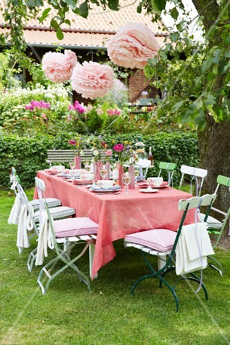A table in a garden with a pink tablecloth and pink paper flower decorations