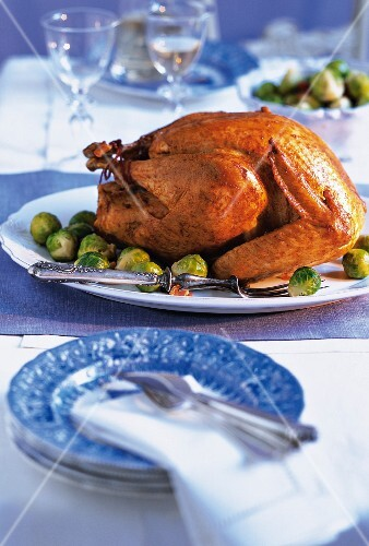 Roast turkey stuffed with dumplings and served with Brussels sprouts