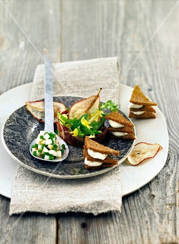 Black bread canapes with cream cheese, pears and beans