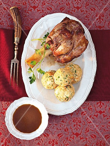 Veal shank with ciabatta dumplings in serving dish, overhead view