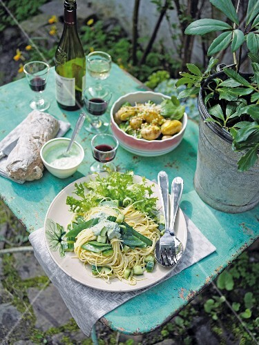 Cucumber-noodle salad, spinach and potato salad and red wine on a garden table