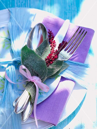 Leaves and knotweed flowers tied with cutlery and napkin on plate
