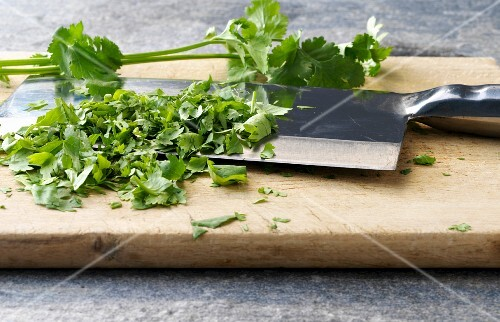 Coriander being chopped on a wooden board