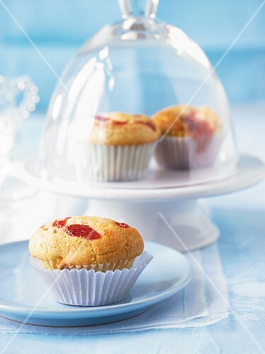 Jam muffins on a plate and under a glass cloche
