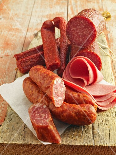 Various types of ham and salami on a wooden board