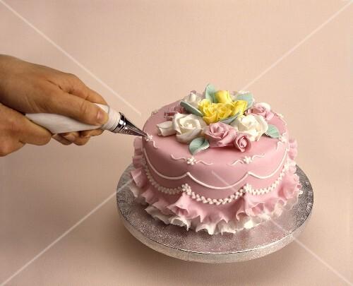 Hochzeitstorte mit Zuckerguß verzieren – StockFood