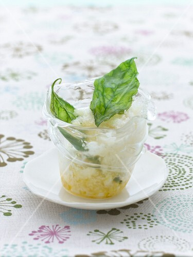 Tomatoes snow in a glass with fried basil leaves