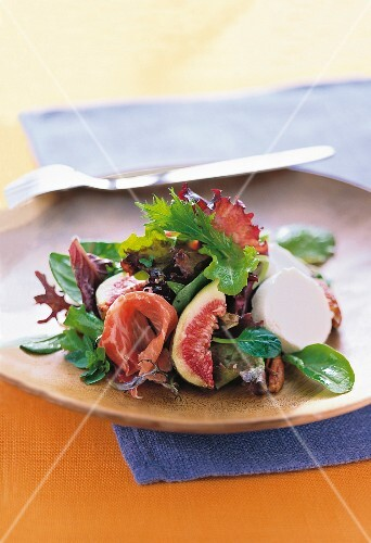 Arugula salad with figs, parma ham and fresh goat cheese on plate