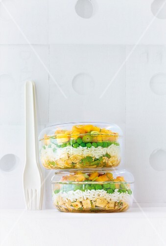 Rice salad with mango and tofu in transparent box kept on table