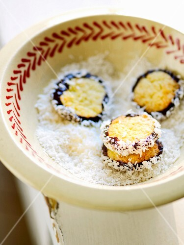 Coconut macaroons in a bowl of grated coconut