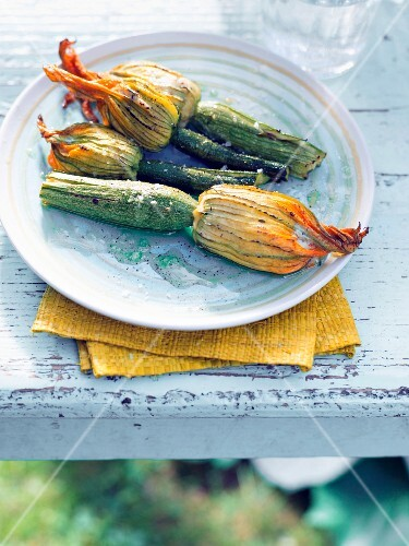 Stuffed courgette flowers on a table outside